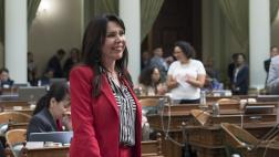 Assemblywoman Rubio smiling while standing at her desk on the Assembly Floor