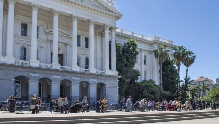 Assemblymembers kneeling outside the state capitol in a tribute to George Floyd