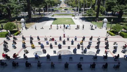 Overhead shot of Assemblymembers kneeling outside the state capitol in a tribute to George Floyd